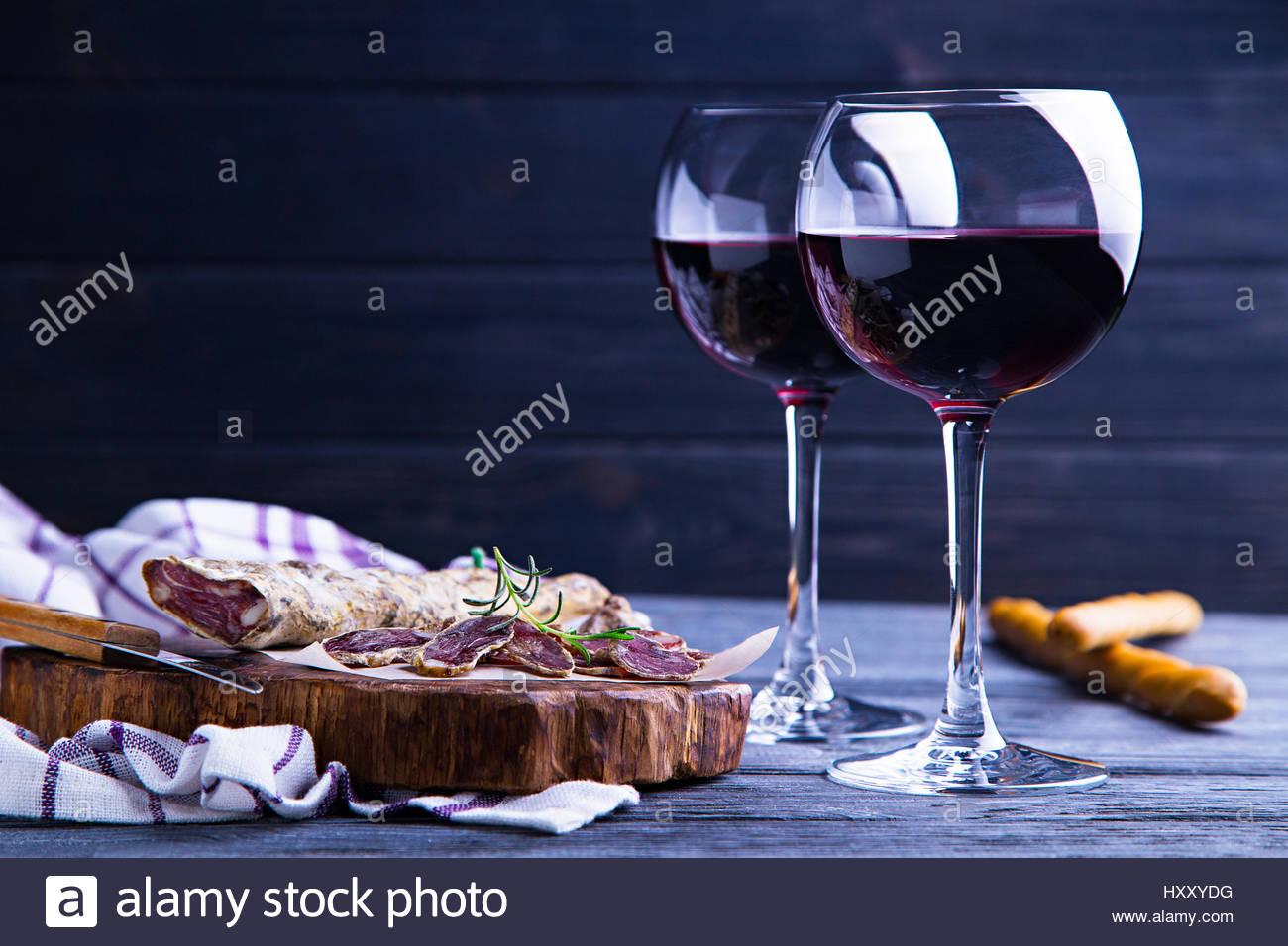 Glas Rotwein mit Salami und grissini Stockbild