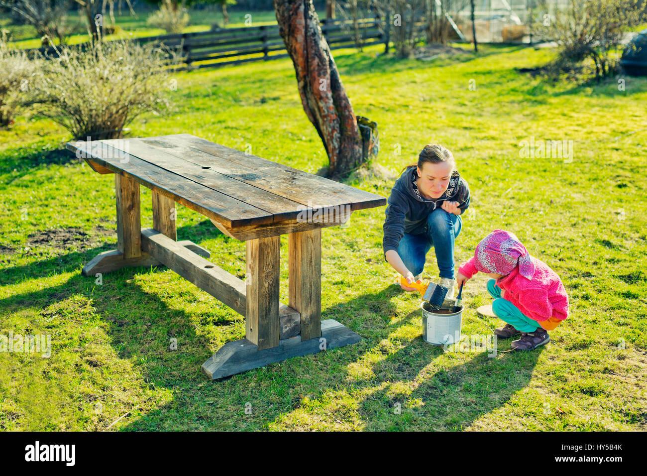Finnland, paijat-Hame, Heinola, Mutter mit Tochter (4-5) ölen Holztisch in Garten Stockbild