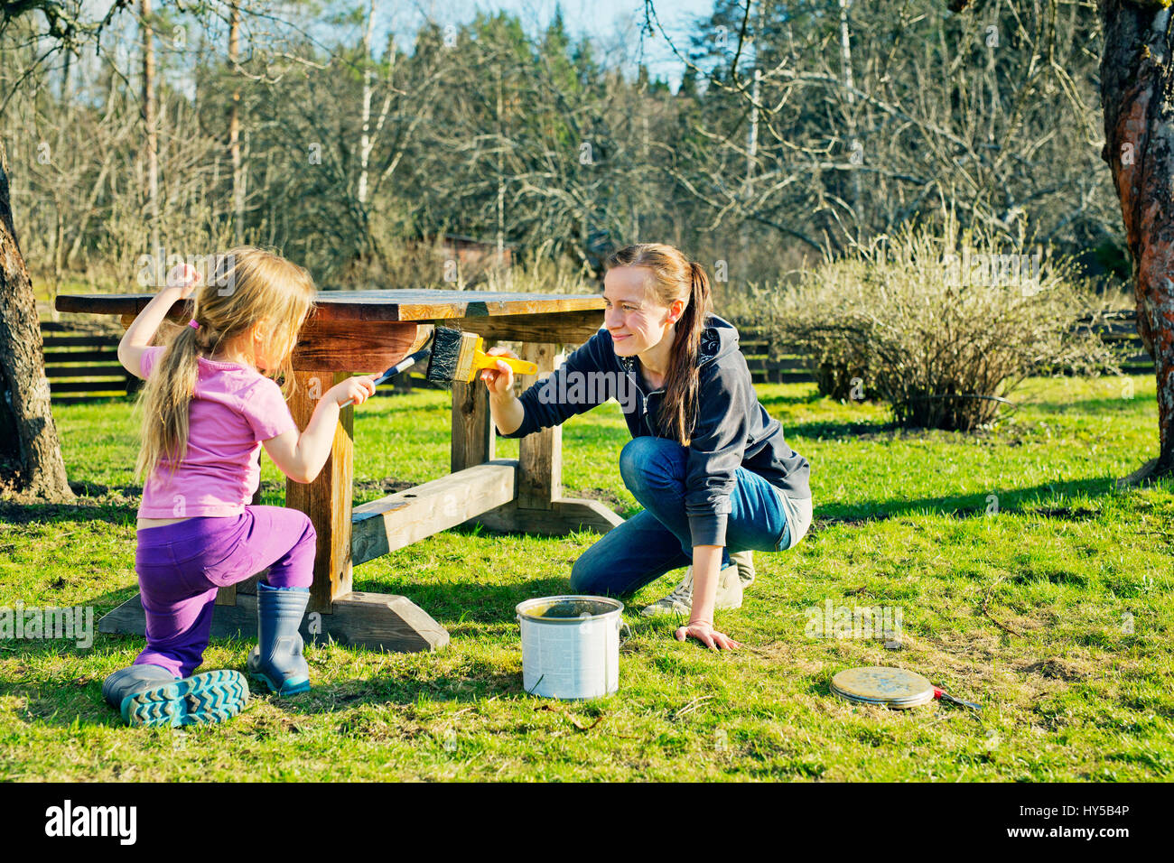 Finnland, paijat-Hame, Heinola, Mutter mit Tochter (4-5) Malerei Holztisch in Garten Stockbild