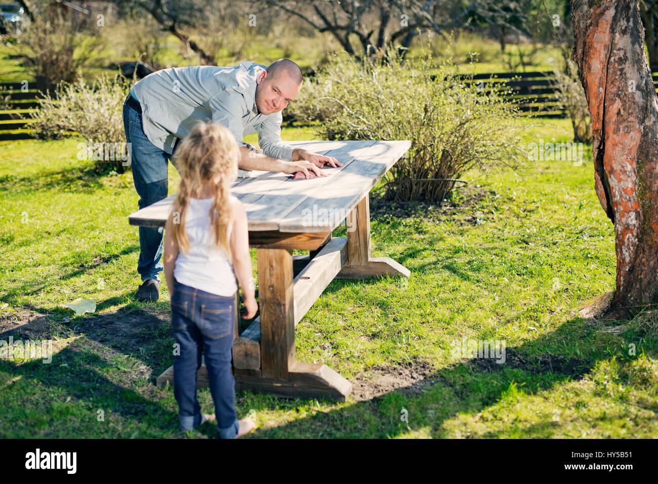 Finnland, paijat-Hame, Heinola, Vater mit Tochter (4-5) polieren Holztisch in Garten Stockbild