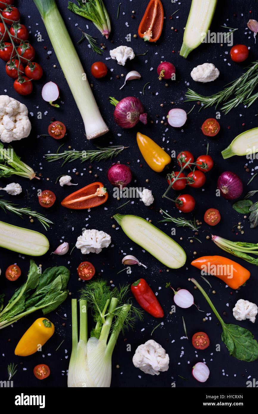Kochen und Würzen von Zutaten über schwarz. Bunte Gemüse über hölzerne Hintergrund. Gesunde Stockbild