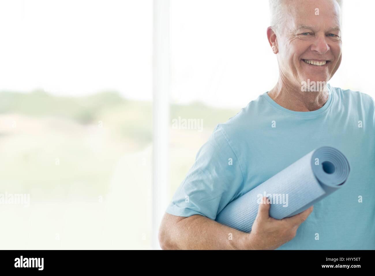 Ältere Mann, der Yoga-Matte. Stockbild