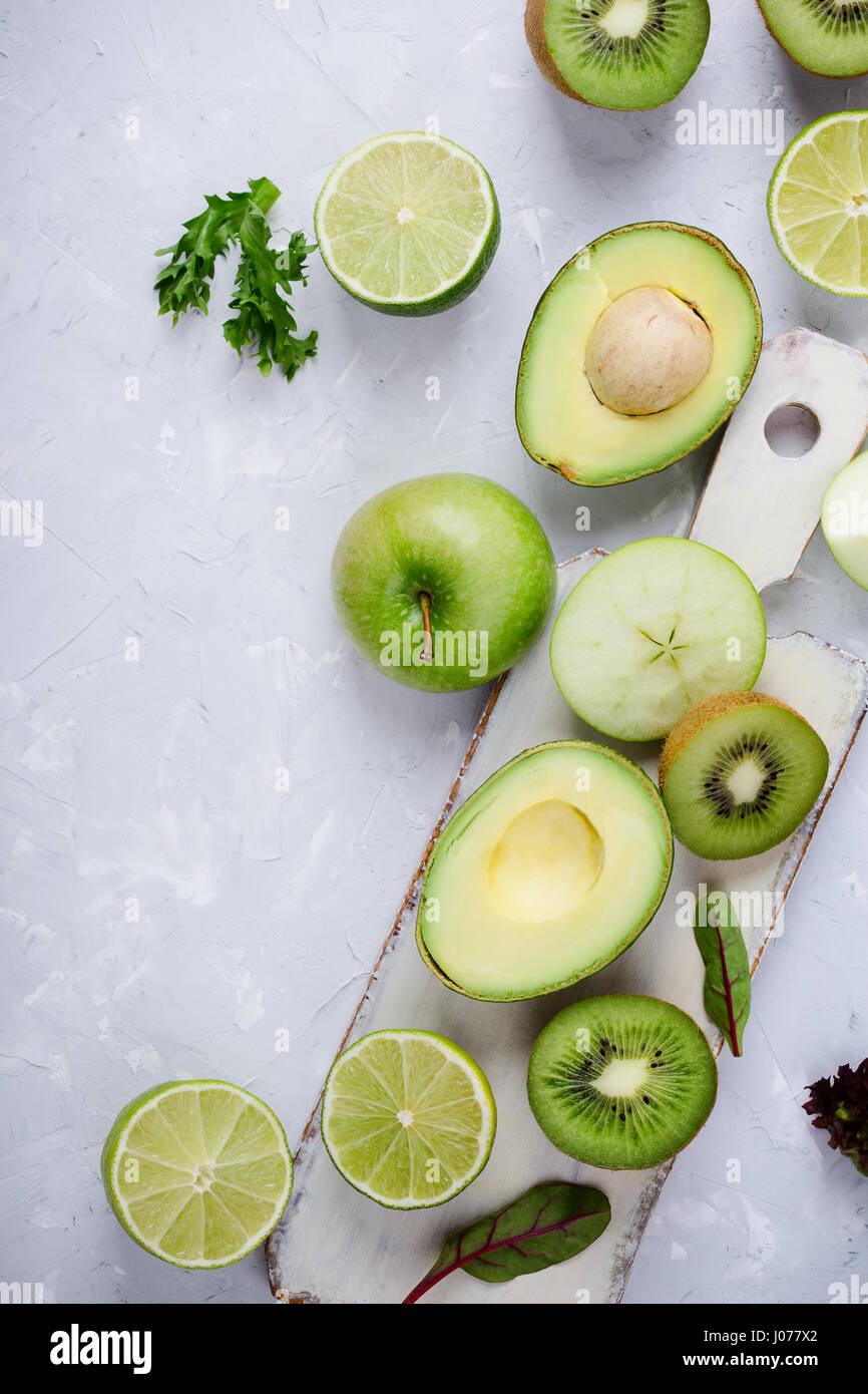 Rahmen der grüne Gemüse und Früchte weiß Holzbrett über leichte graue Putz Tisch, Essen Stockbild