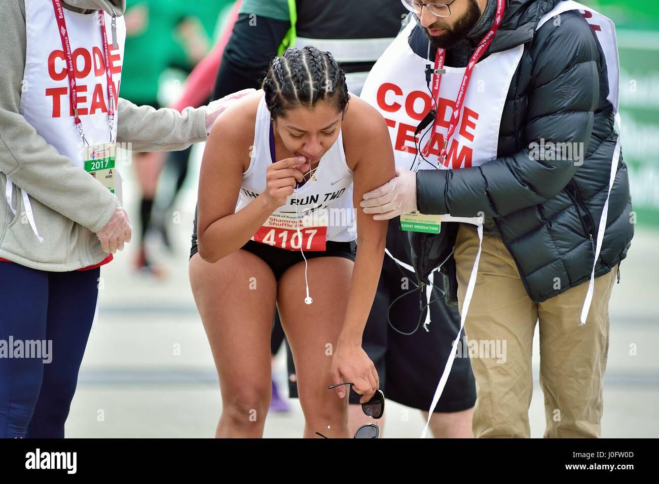 Nach dem Überqueren der Ziellinie am 2017 Shamrock Shuffle Rennen in Chicago eine Läuferin ärztliche Stockbild