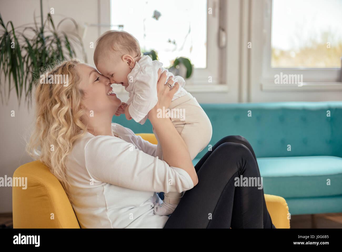 Mutter und Baby Kopf-an-Kopf sitzen am gelben Sessel Stockbild