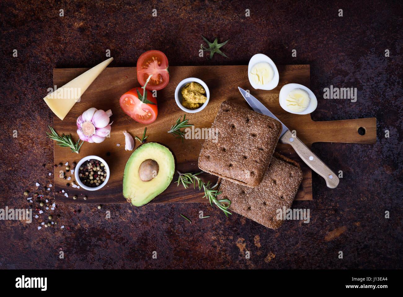 Veggie-Burger mit Avocado, Käse und Ei auf Holzbrett. Ansicht von oben flach legen. Bio-Brot. Stockbild