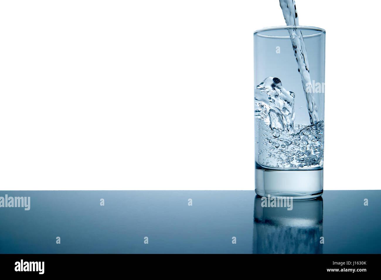 Frisches Wasser gegossen in ein Glas mit Exemplar, isoliert und blau getönt Stockbild