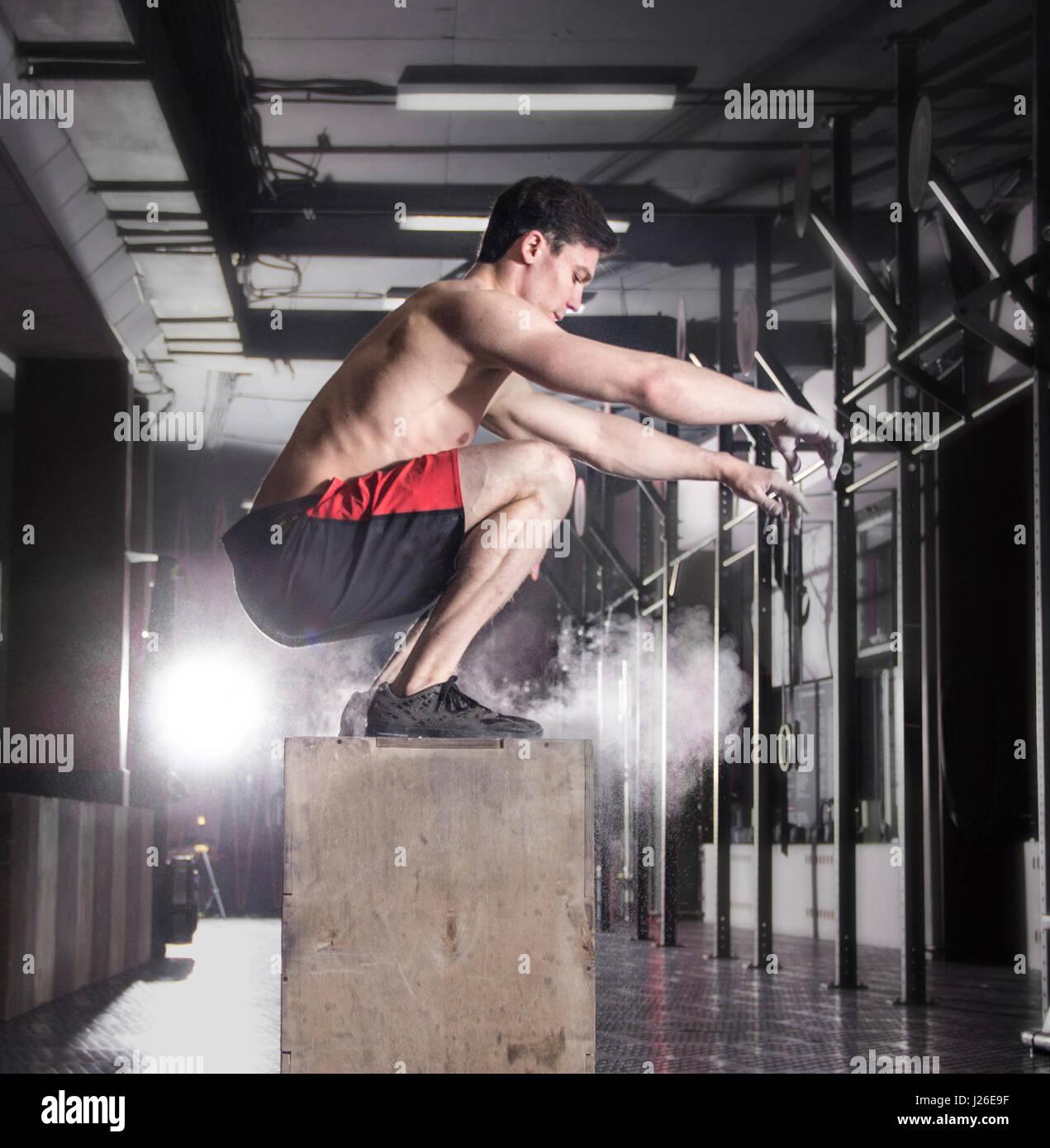 Passen Sie junge Männer-Kiste springen in einem Crossfit Gym. Sportler Datenzugriffsmöglichkeit Stockbild