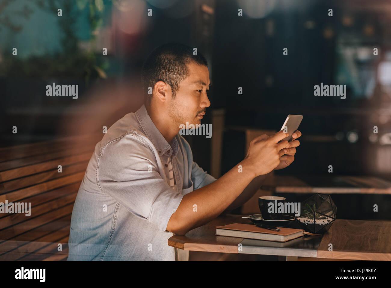 Junge asiatische Mann sitzen in einem Café, im Internet surfen Stockbild