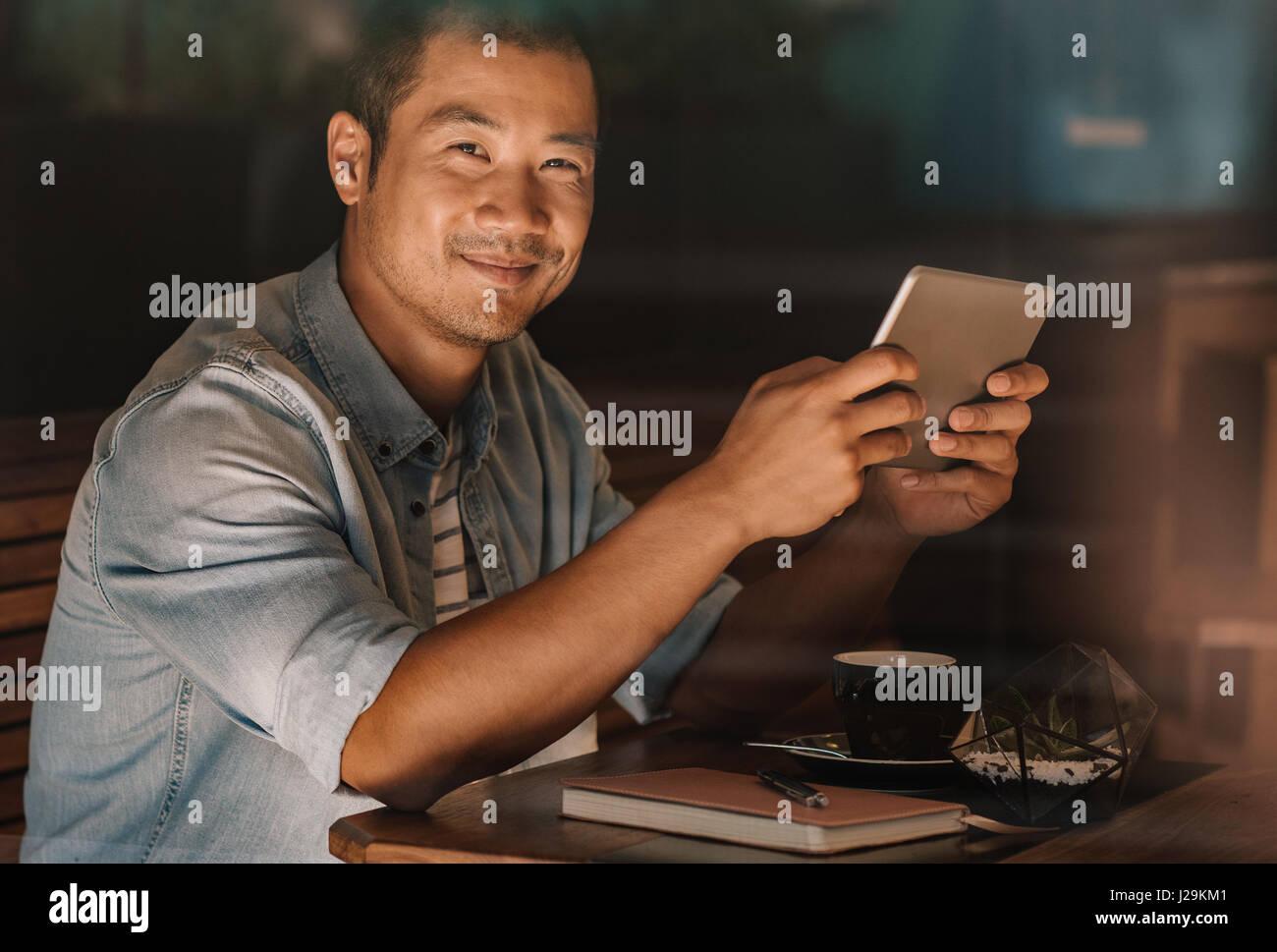 Content-asiatischen Mann, Surfen im Internet, beim Sitzen in einem café Stockbild