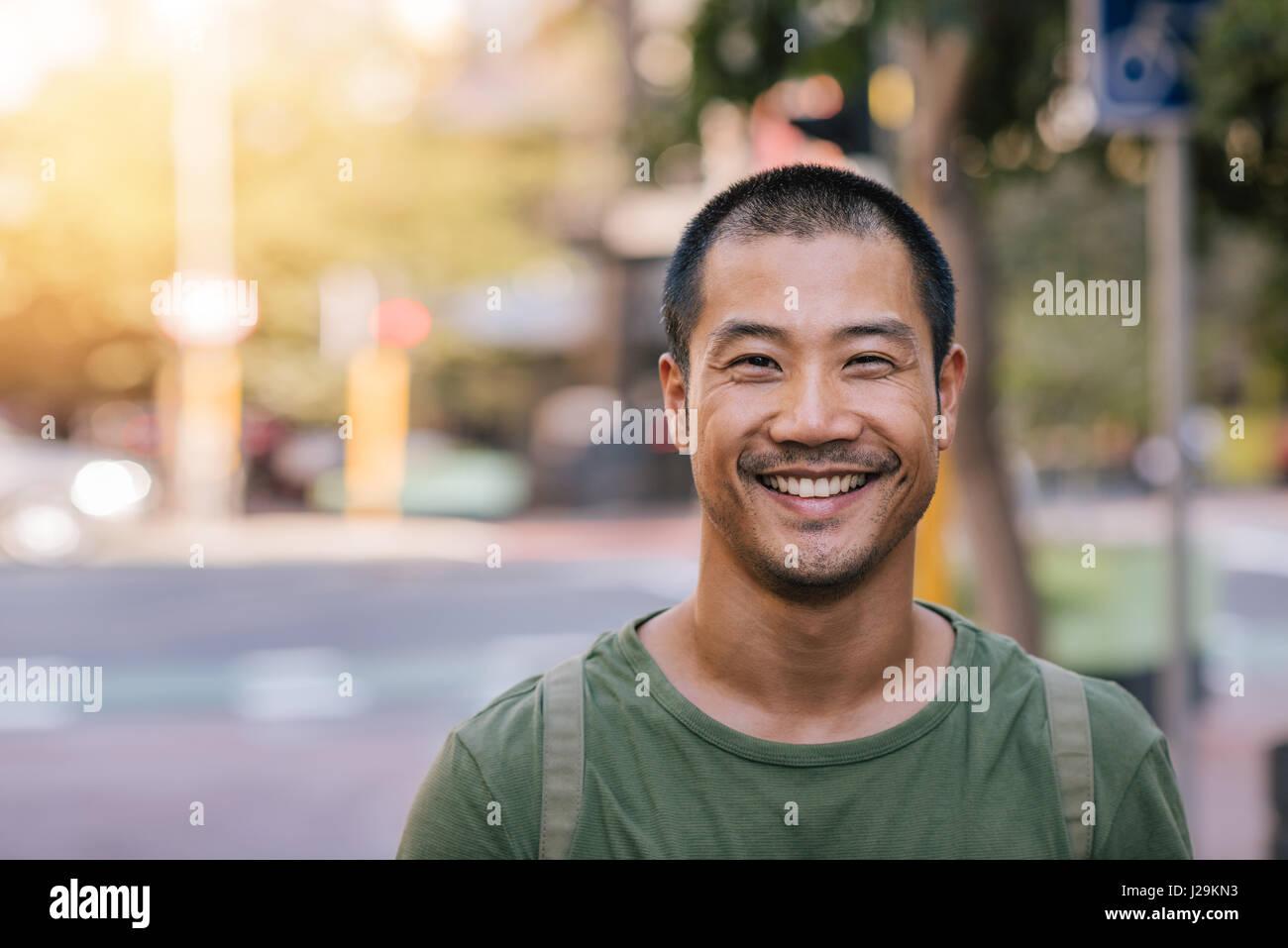 Junge asiatische Mann lächelnd souverän auf einer Stadtstraße Stockbild