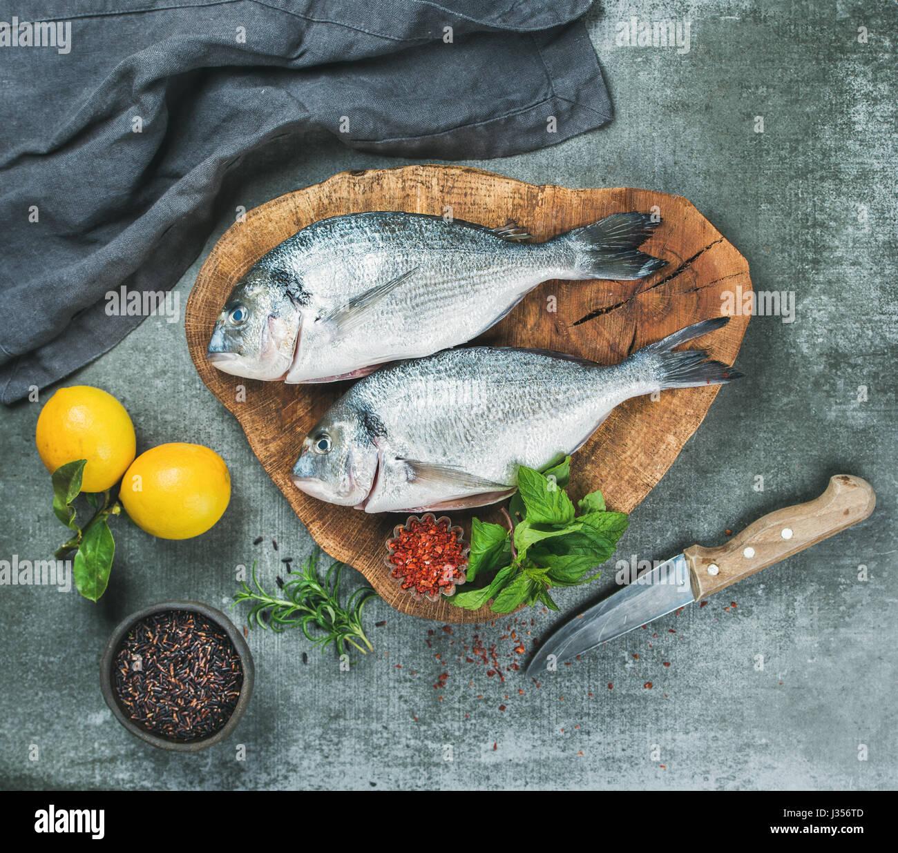 Ungekocht Dorade Fisch mit Zitrone, Kräuter, Gewürze, grauen Hintergrund Stockbild