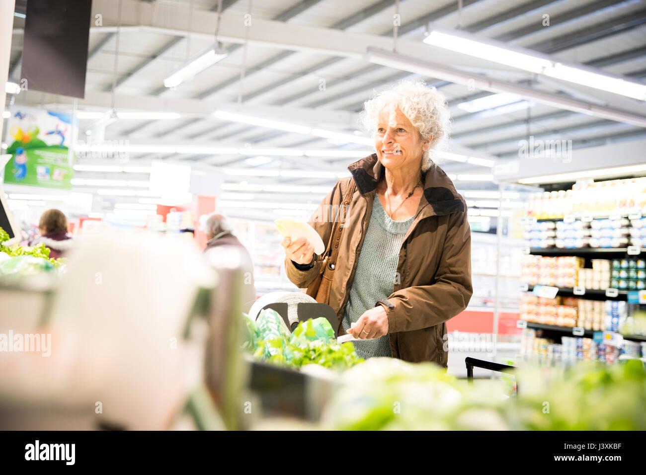 Reife Frau im Supermarkt, der frische Produkte Stockbild
