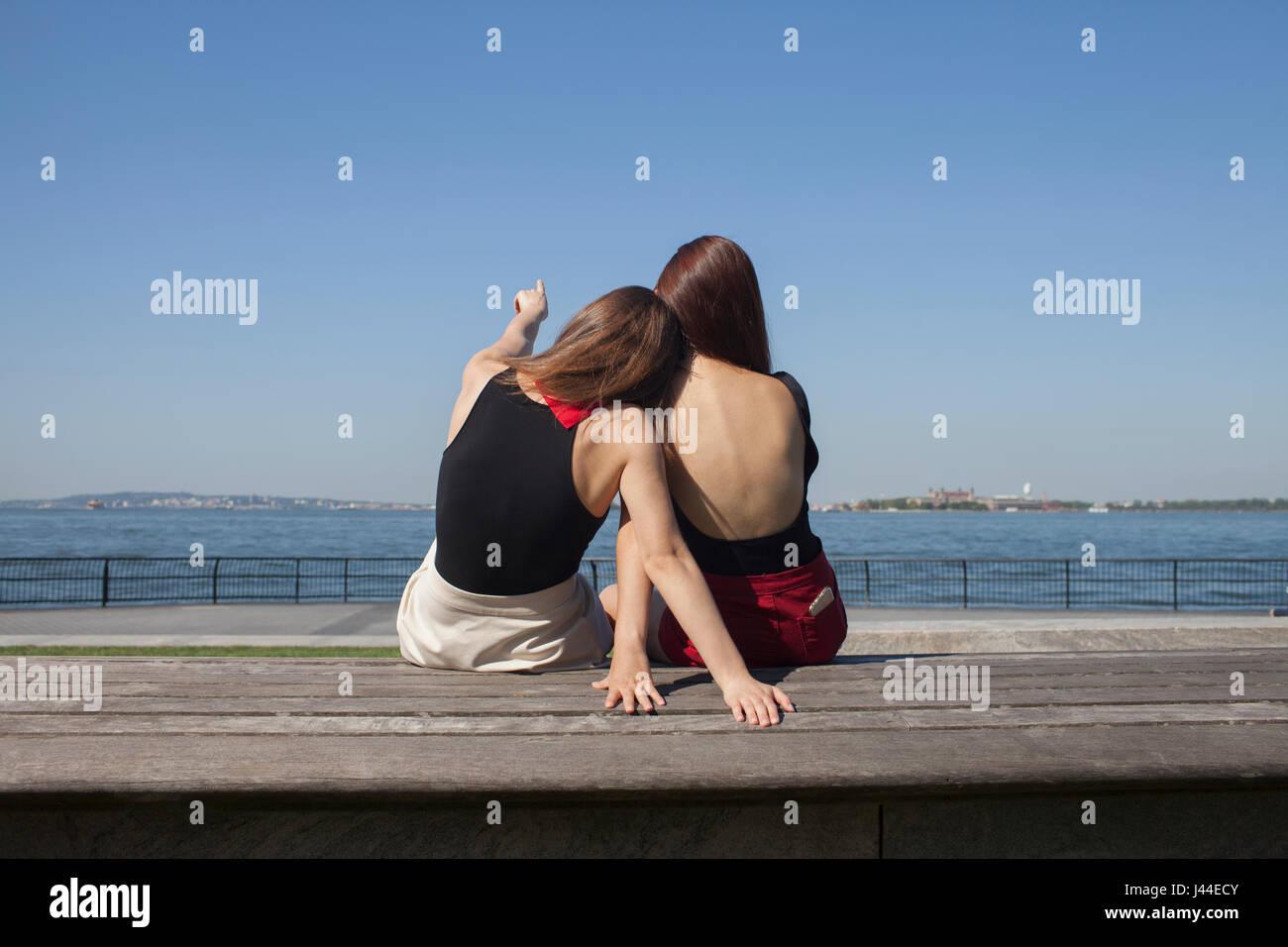 Rückansicht der beiden jungen Frauen sitzen Stockbild