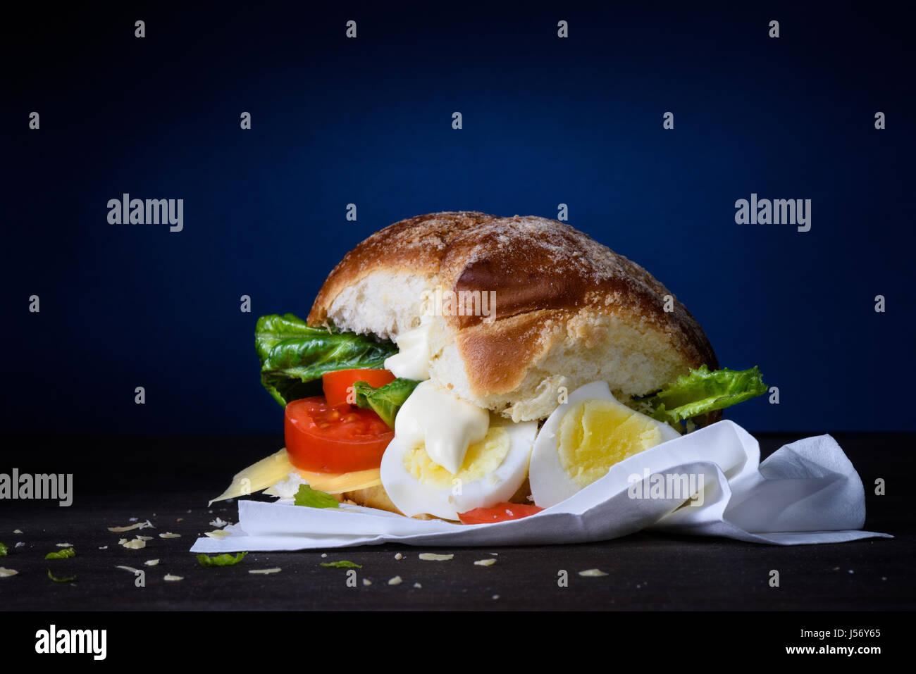 Leckere Burger mit Ei, Tomaten, Käse, Salat und Mayonnaise auf hölzernen Theke. Kopieren Sie Raum. Stockbild
