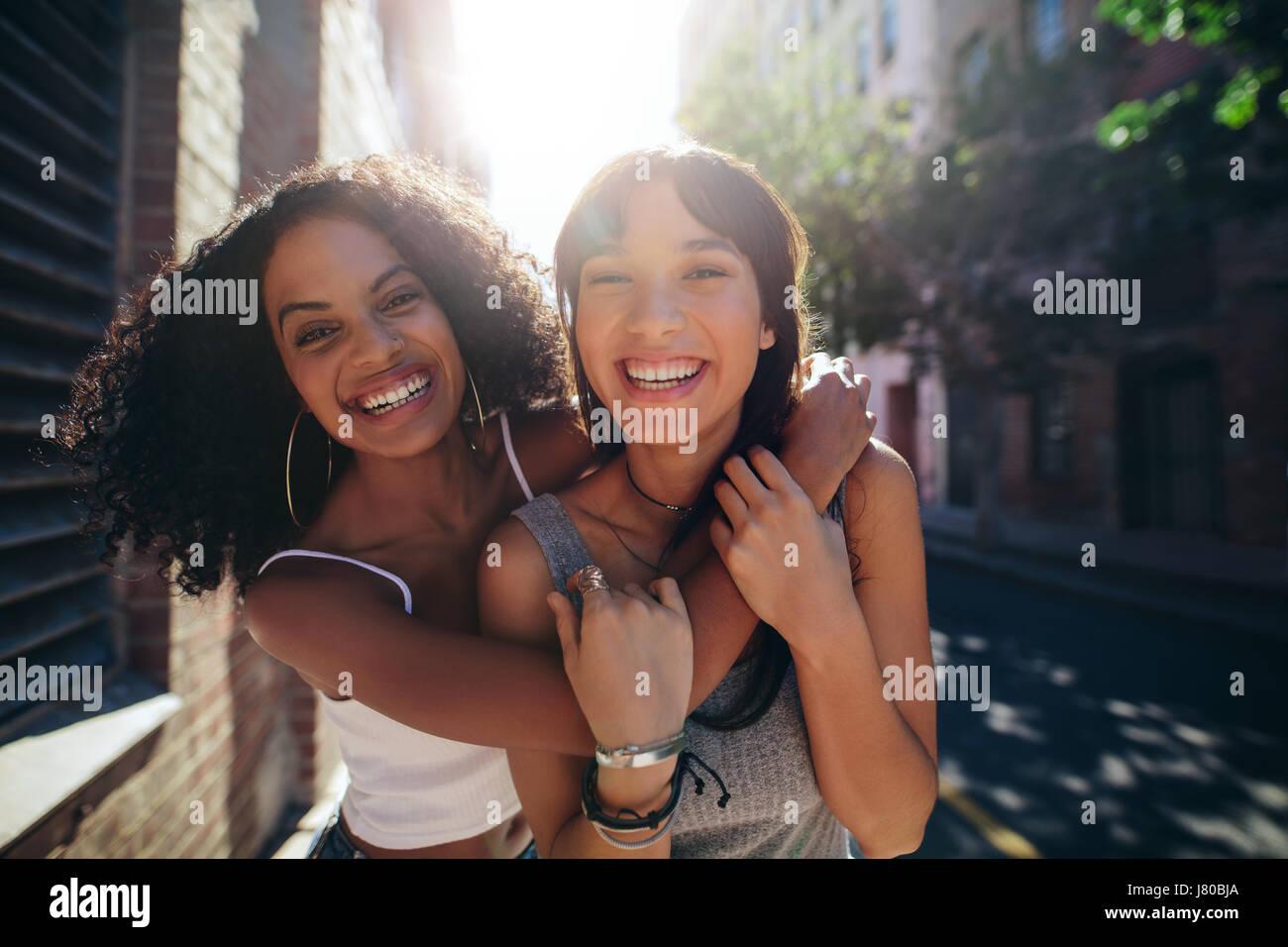 Porträt von zwei jungen Frauen auf Stadtstraße Spaß. Freundinnen umarmen und lächelnd im Freien Stockbild