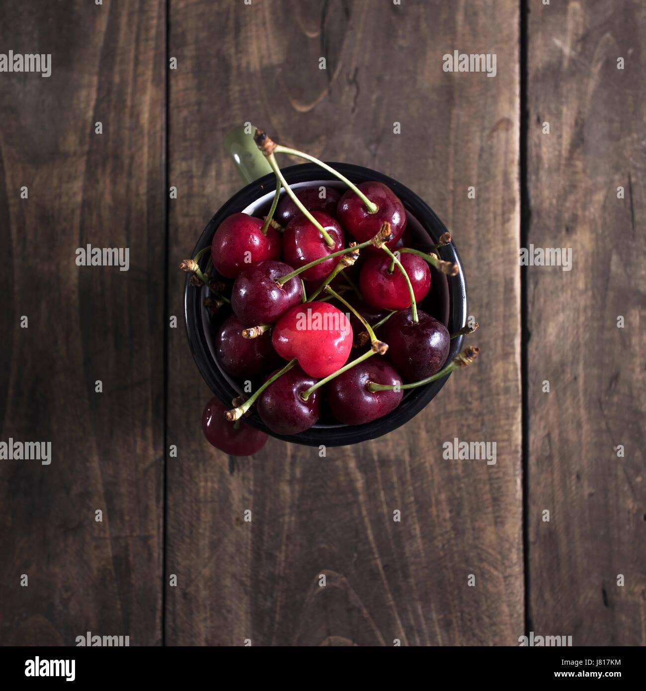 Frisch gepflückten Kirschen auf dunklen Holztisch von oben Stockbild