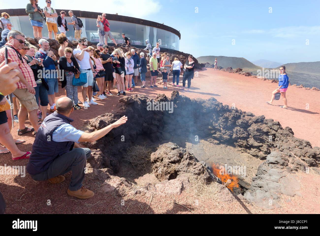 Lanzarote-Nationalpark Timanfaya - Demonstration der vulkanischen Aktivität an Touristen, Nationalpark Timanfaya, Stockbild