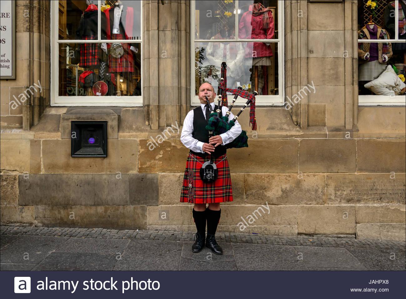 Ein schottischer Dudelsackspieler in traditionellen Kilt unterhält Passanten, von die viele Touristen, auf Stockbild
