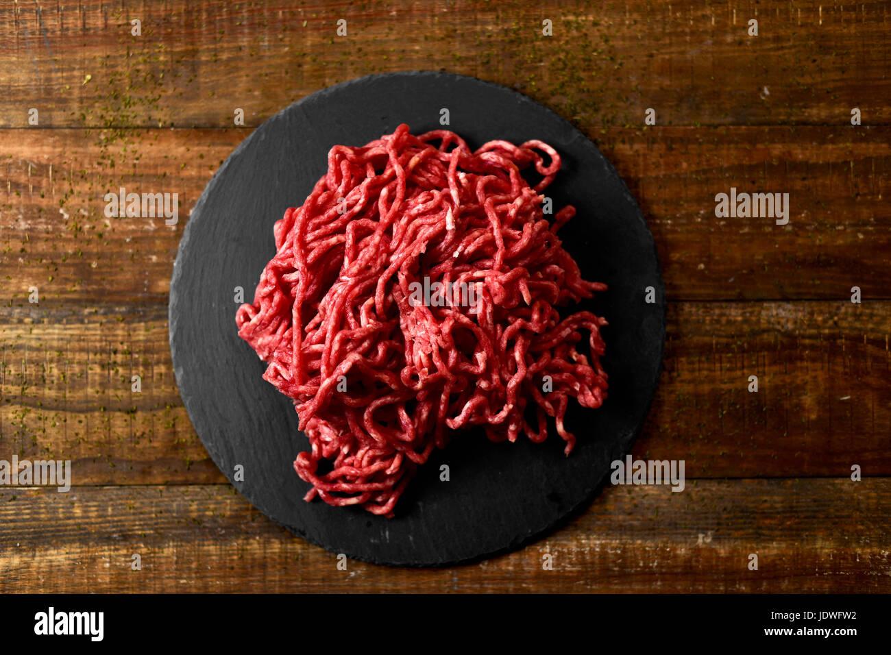High-Angle Shot von einem Haufen von rohes Rindfleisch Hackfleisch auf einem Schiefer Teller, platziert auf einem Stockbild