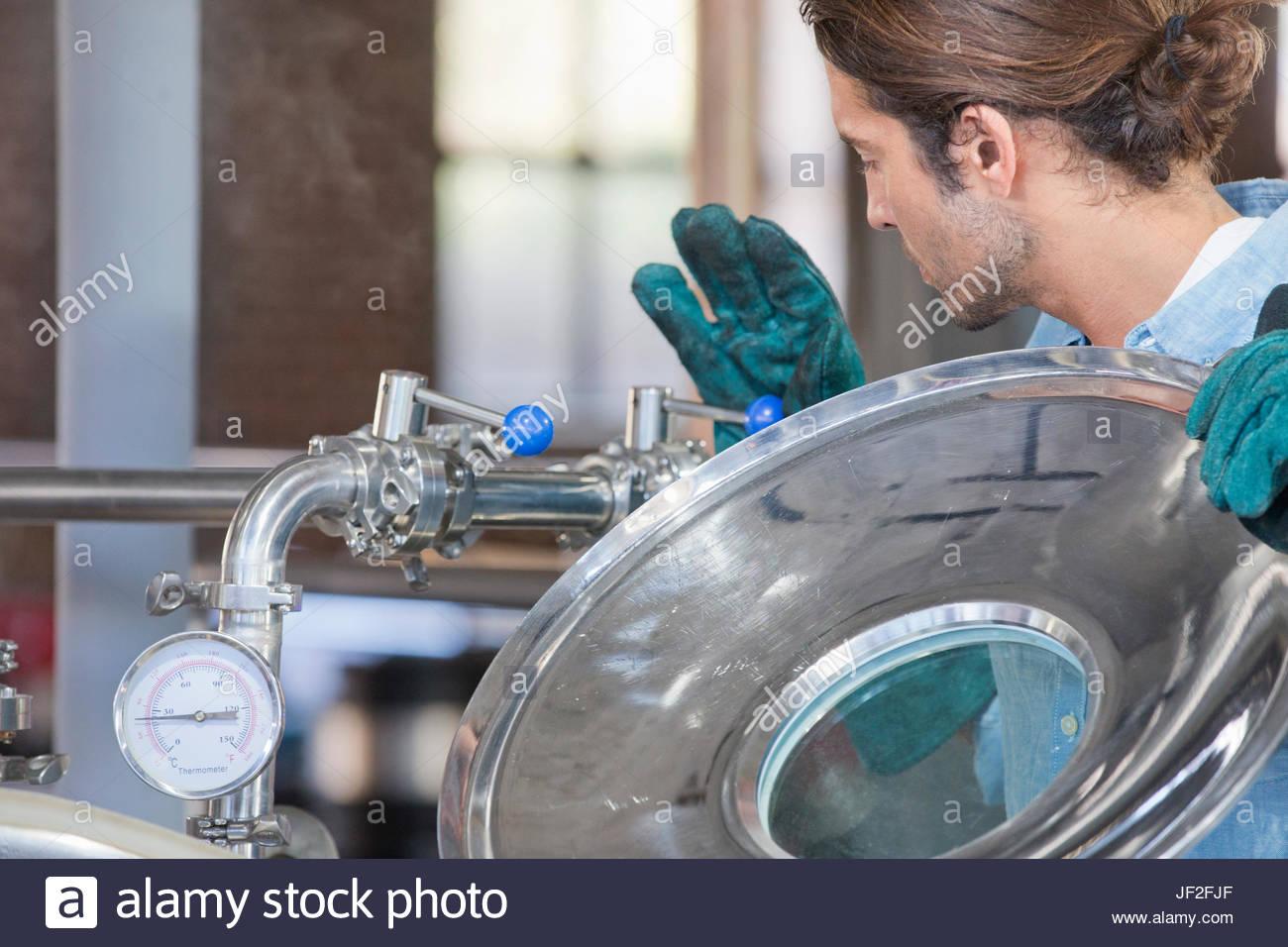 Männliche Brauerei Worker Fermentationsprozess In Stahl Mehrwertsteuer überprüfen Stockbild