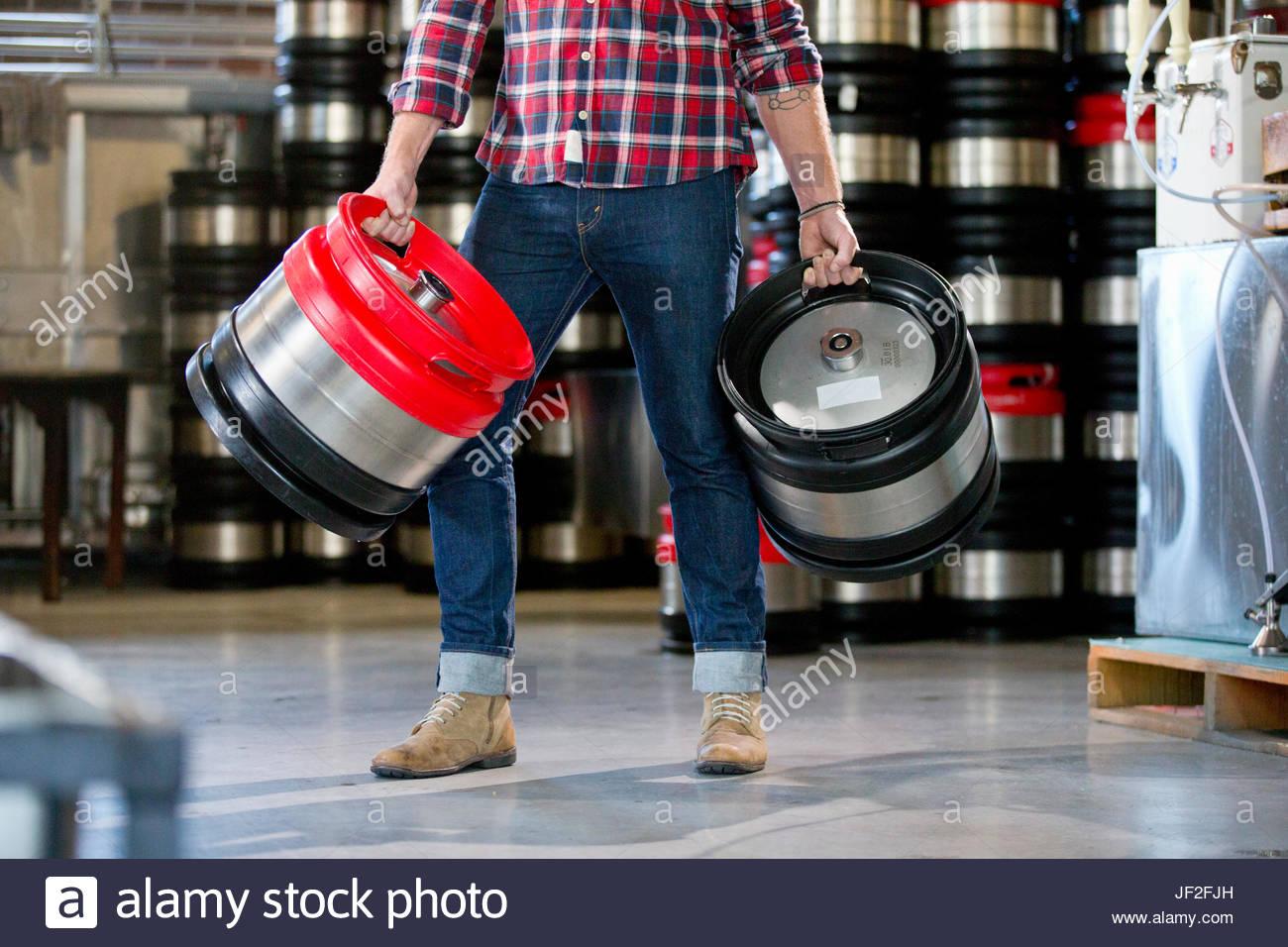Detail der männlichen Brauerei Arbeiter tragen Bierfässer im Abstellraum Stockbild