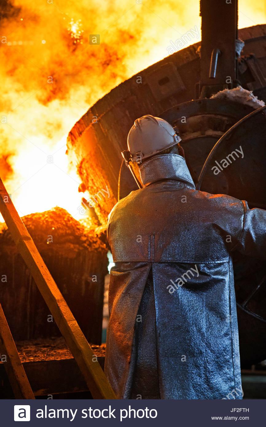 Arbeiter In Schutzkleidung gießt geschmolzenes Metall In Gießerei Stockbild
