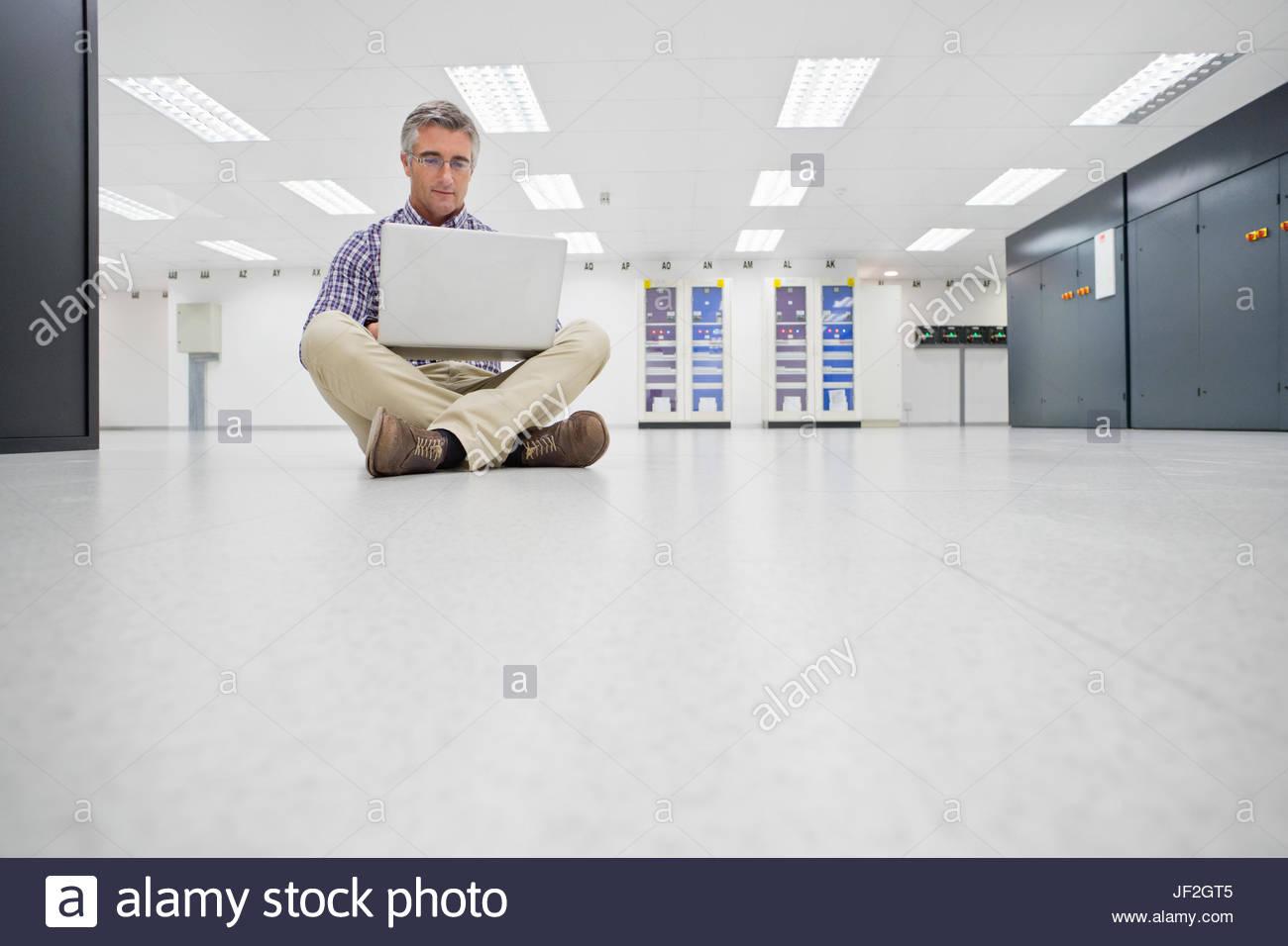 Techniker sitzen am Boden Laptop arbeiten im Rechenzentrum Stockbild