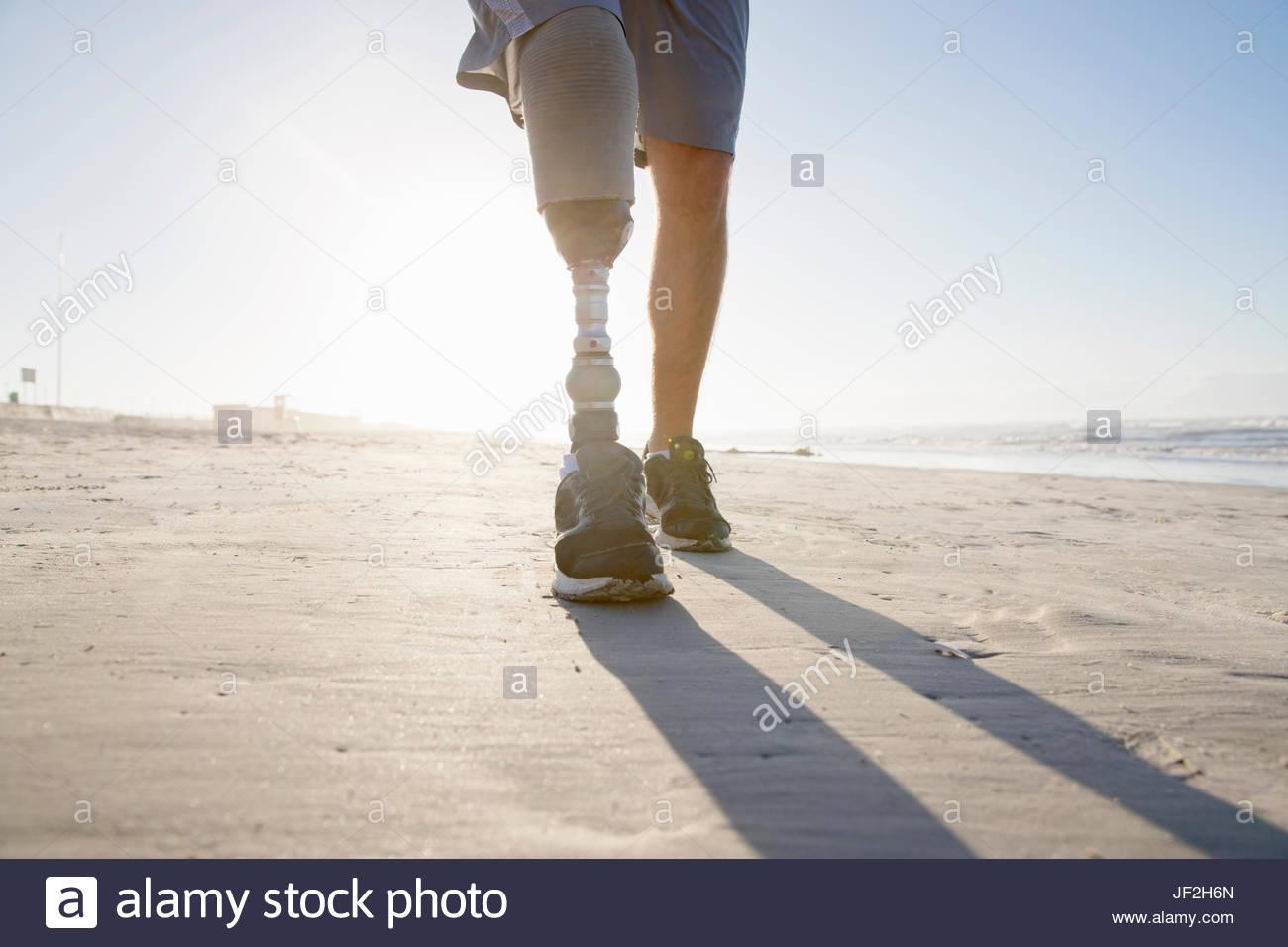 Nahaufnahme von Mann mit Beinprothese Strand entlang laufen Stockbild