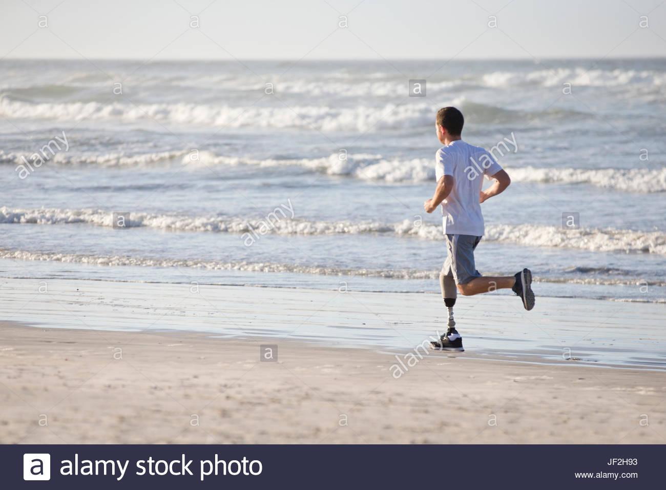 Mann mit Beinprothese Strand entlang laufen Stockbild