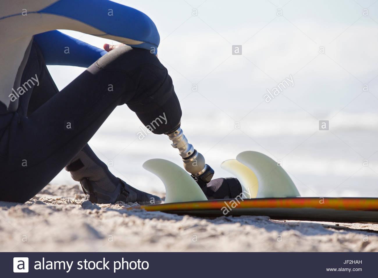 Nahaufnahme von Surfer mit künstlichem Bein sitzen am Strand Stockbild