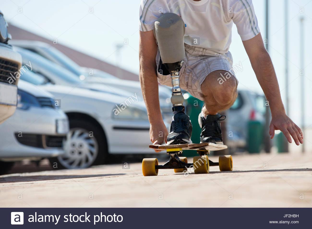 Nahaufnahme von Mann mit Beinprothese mit Skateboard Stockbild
