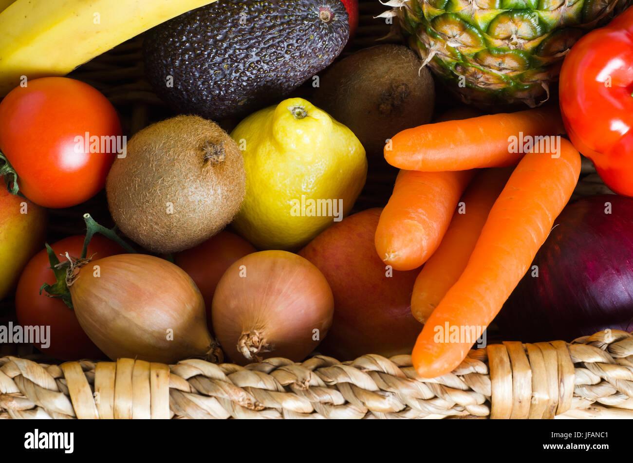 Overhead Schuss eines Korbs vollgestopft mit rohen, frischen, bunten Obst und Gemüse.  Im Querformat. Stockbild