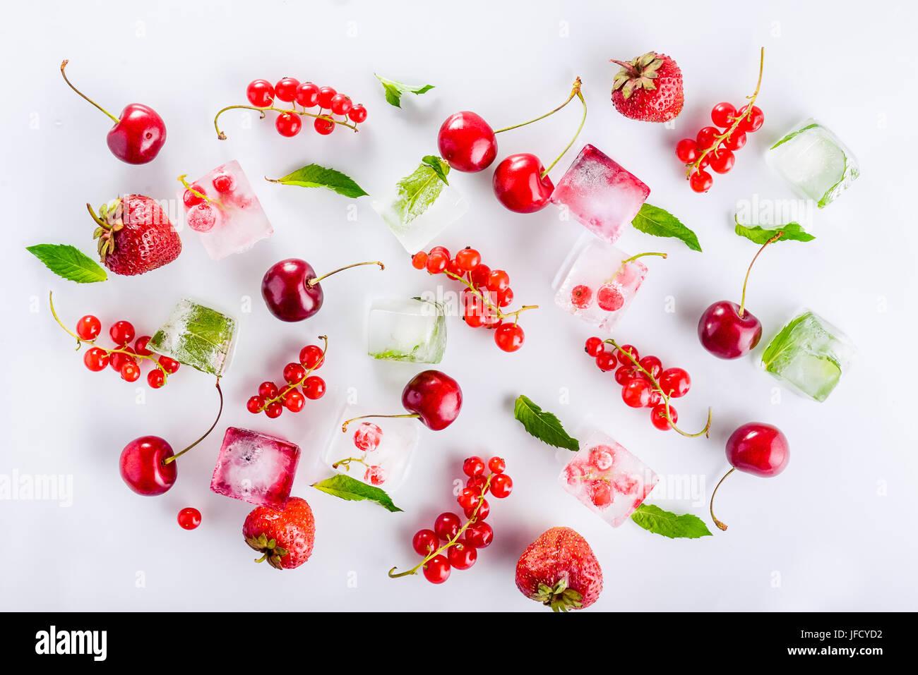 Draufsicht auf Eiswürfel mit frischen Beeren unter nicht gefrorene Kirschen, Erdbeeren und Minze Blätter Stockbild