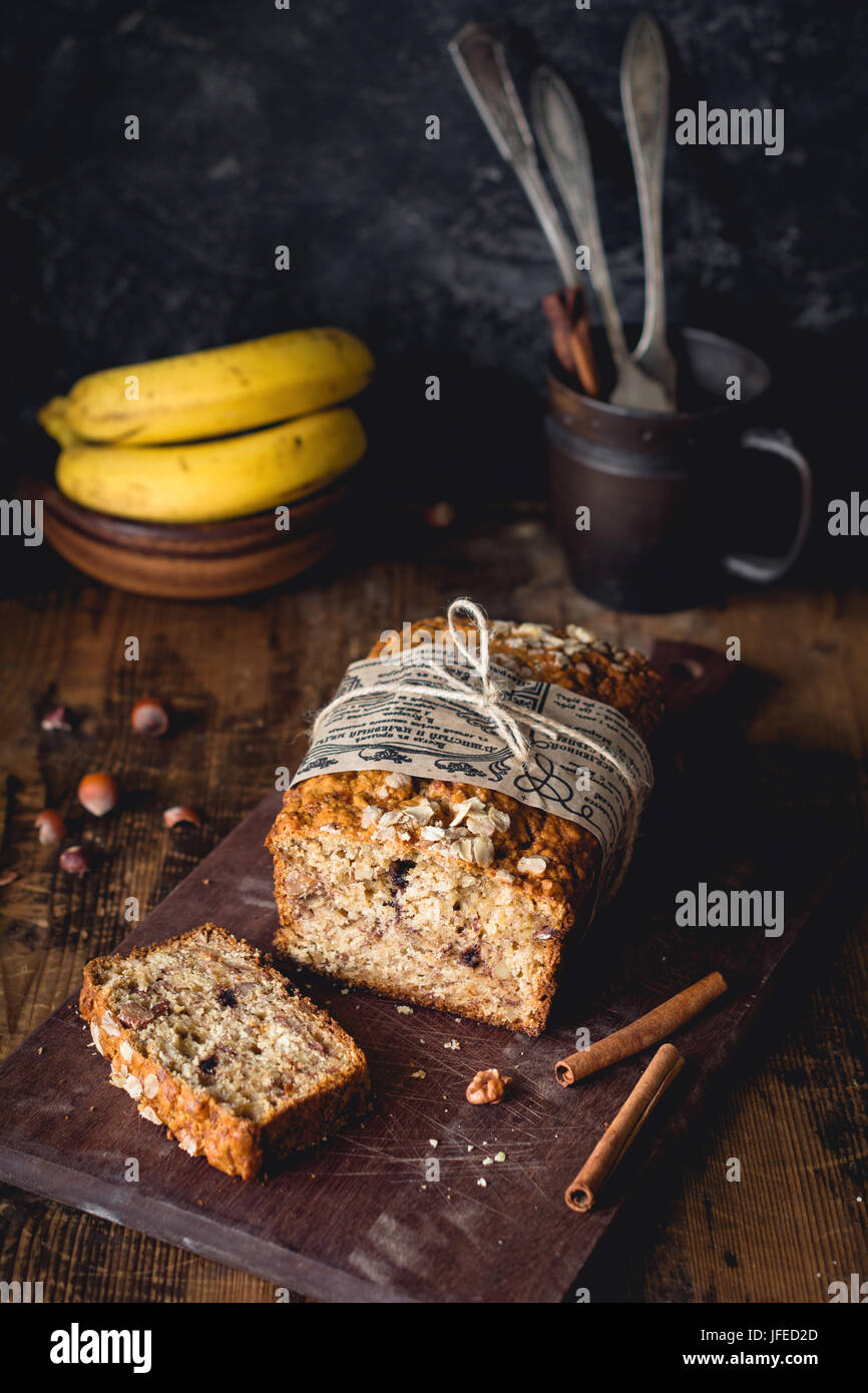 Bananenbrot mit Walnüssen, Zimt und Schokolade-Chips auf Holzbrett. Selektiven Fokus. Essen Stilleben, dunkles Stockbild