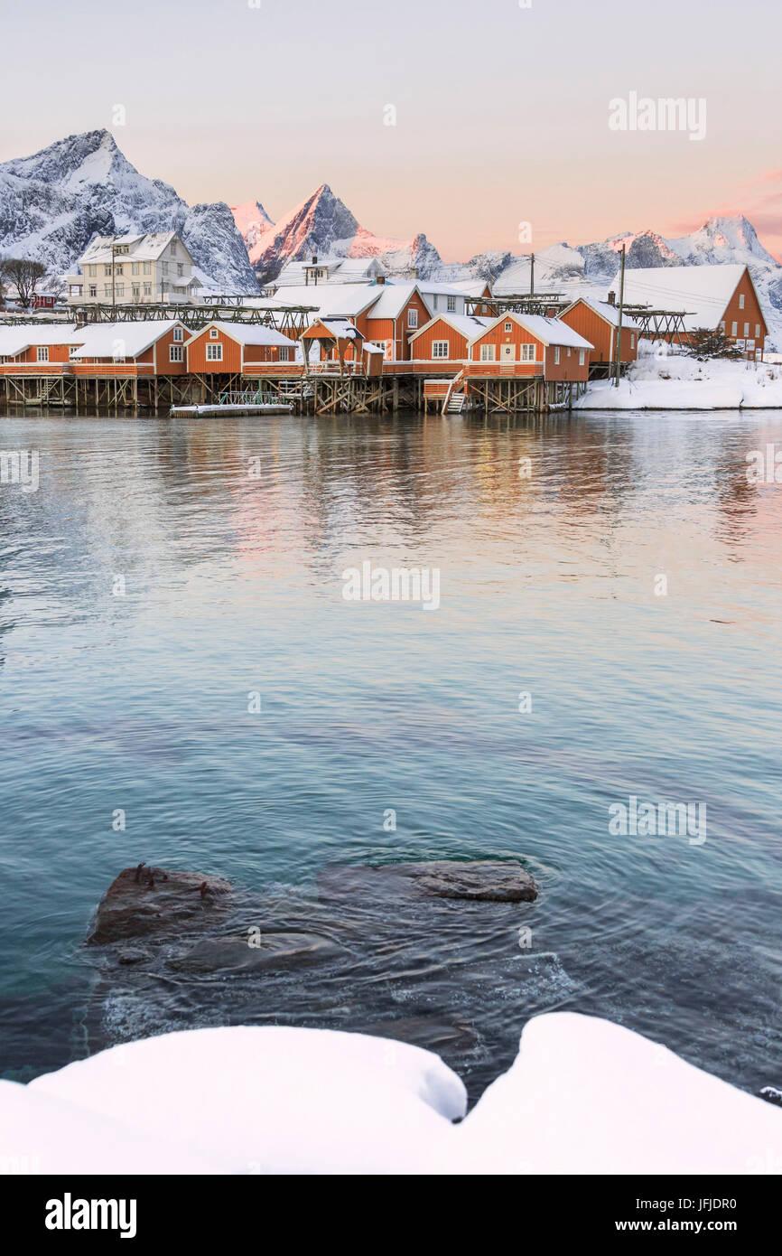 Die Farben der Morgenröte rahmt die Fischerhäuser, umgeben von schneebedeckten Gipfeln Sakrisøy Reine Stockbild
