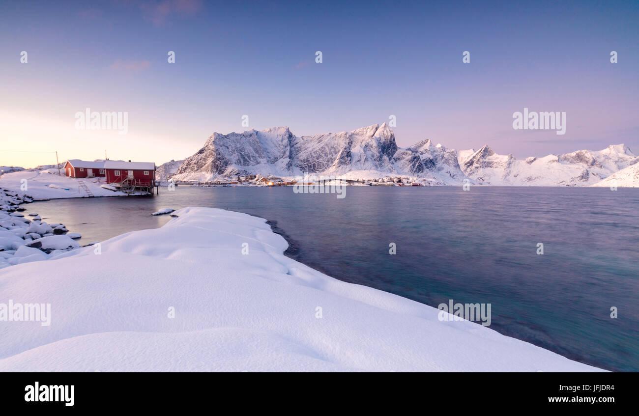 Die Farben der Morgenröte rahmt die Fischerhäuser, umgeben von gefrorenen Meer Sakrisøy Reine Nordland Stockbild