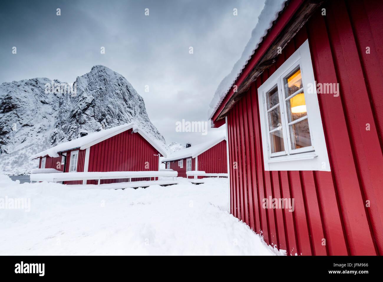 Wolken auf den typischen roten Häusern der Fischer namens Fischerorten umgeben von schneebedeckten Hamnøy Stockbild