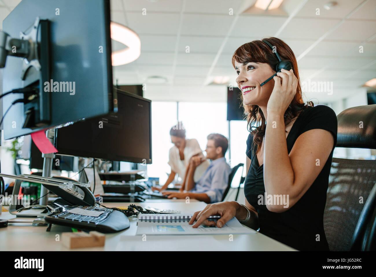 Lässige Geschäftsfrau arbeiten am Schreibtisch mit Computer und Kopfhörer im Büro. Frau sitzt Stockbild