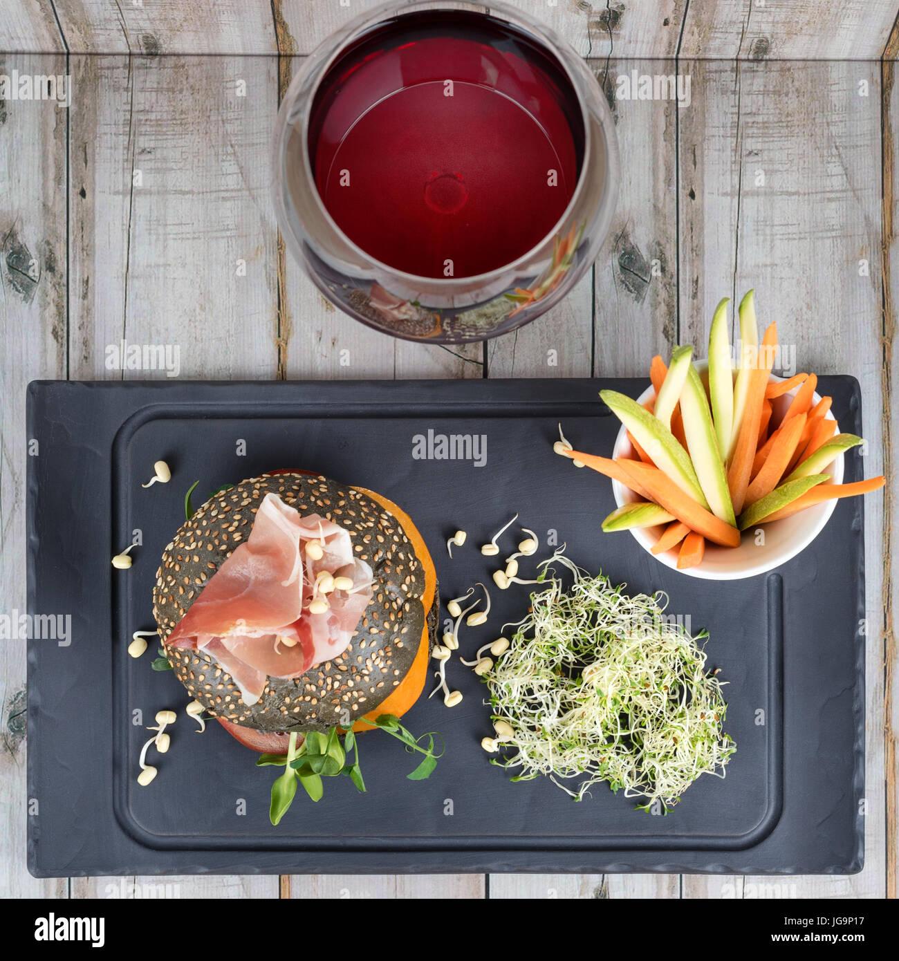 Gesunde Burger mit Hamon, Tomaten, Mikro grünen und schwarzen Vollkorn Brötchen, Gemüsesticks und Stockbild