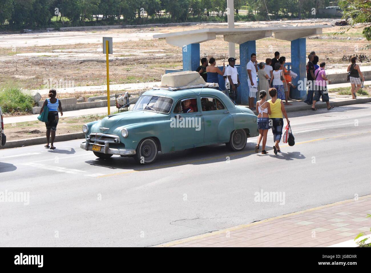 Lokalen Kubaner warten an der Bushaltestelle zur Arbeit als klassische blaue amerikanische Automobile Antriebe durch Stockbild