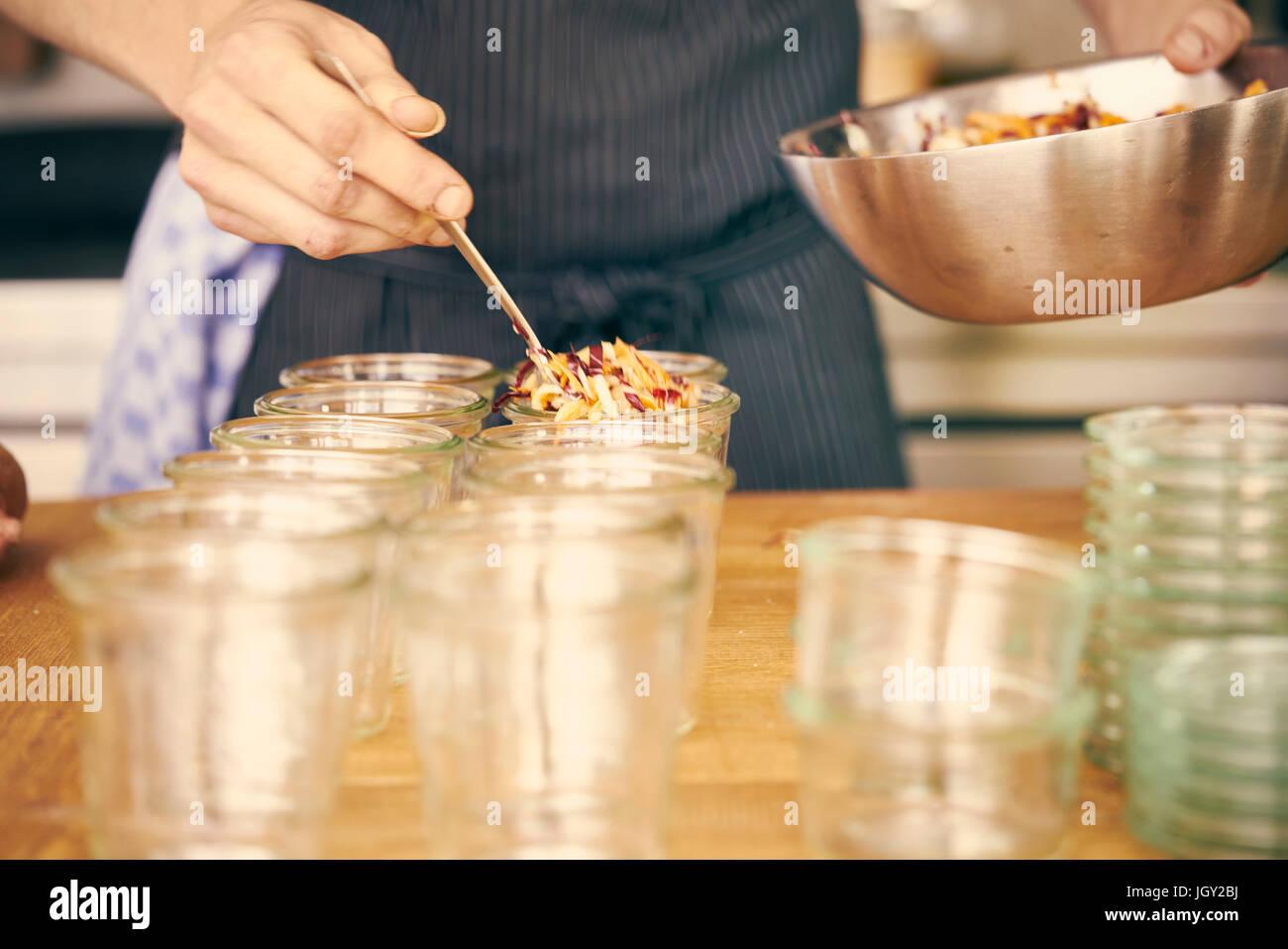 Koch, Kunststoffbehälter mit Portionen von Lebensmitteln zu füllen Stockbild