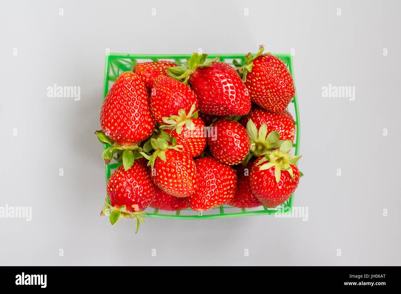 Frische Erdbeeren in einen Kunststoff grün Körbchen auf einem grauen Hintergrund Stockbild