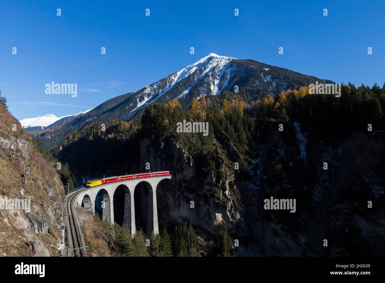 Bernina Express überfährt Landwasser Viadukt umgeben von bunten Wäldern, Kanton Graubünden, Stockbild
