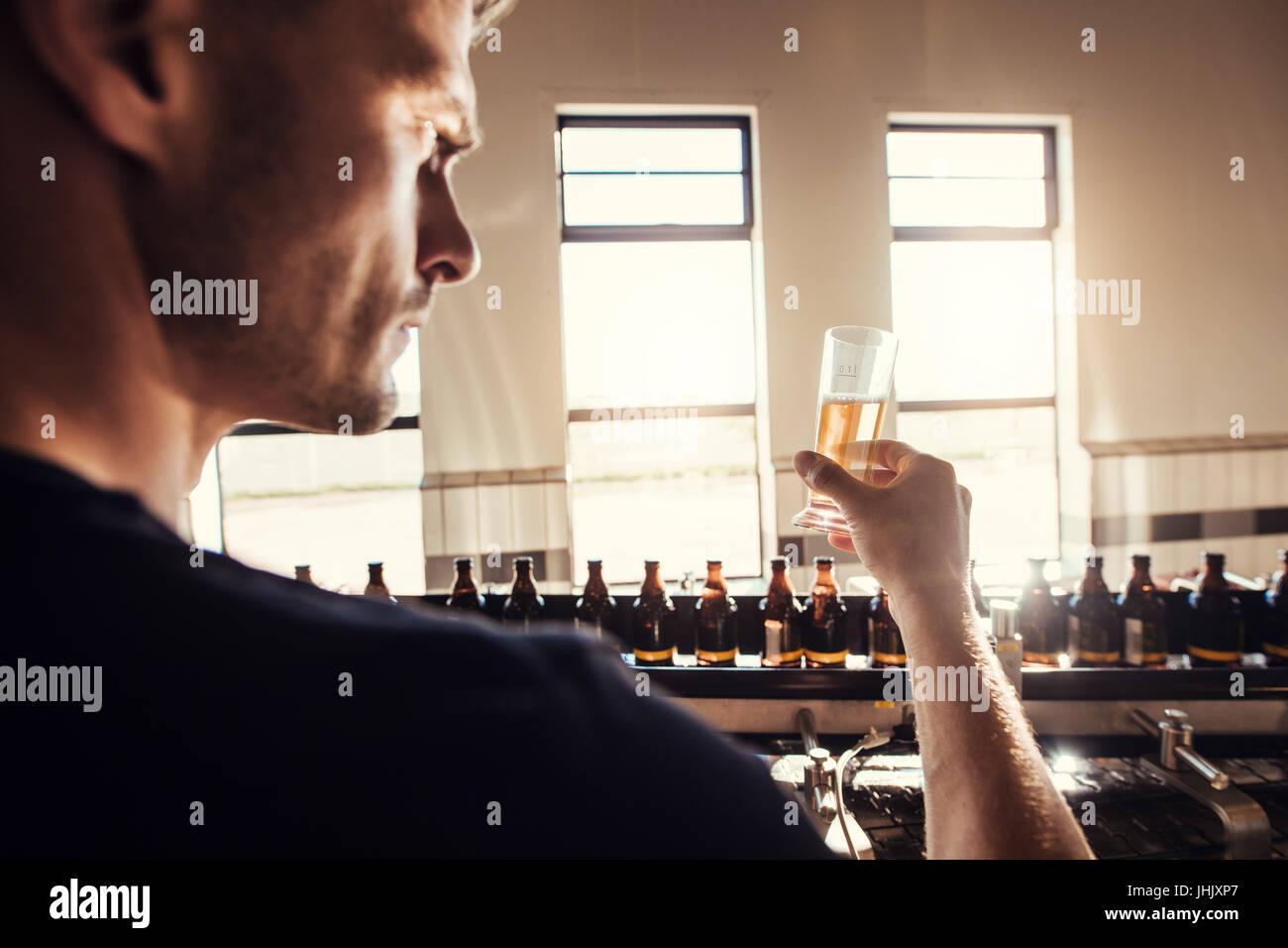 Männliche Brauer Handwerk Bier Brauerei werkseitig getestet. Junger Mann Probe Bierglas während der Fertigung Stockbild