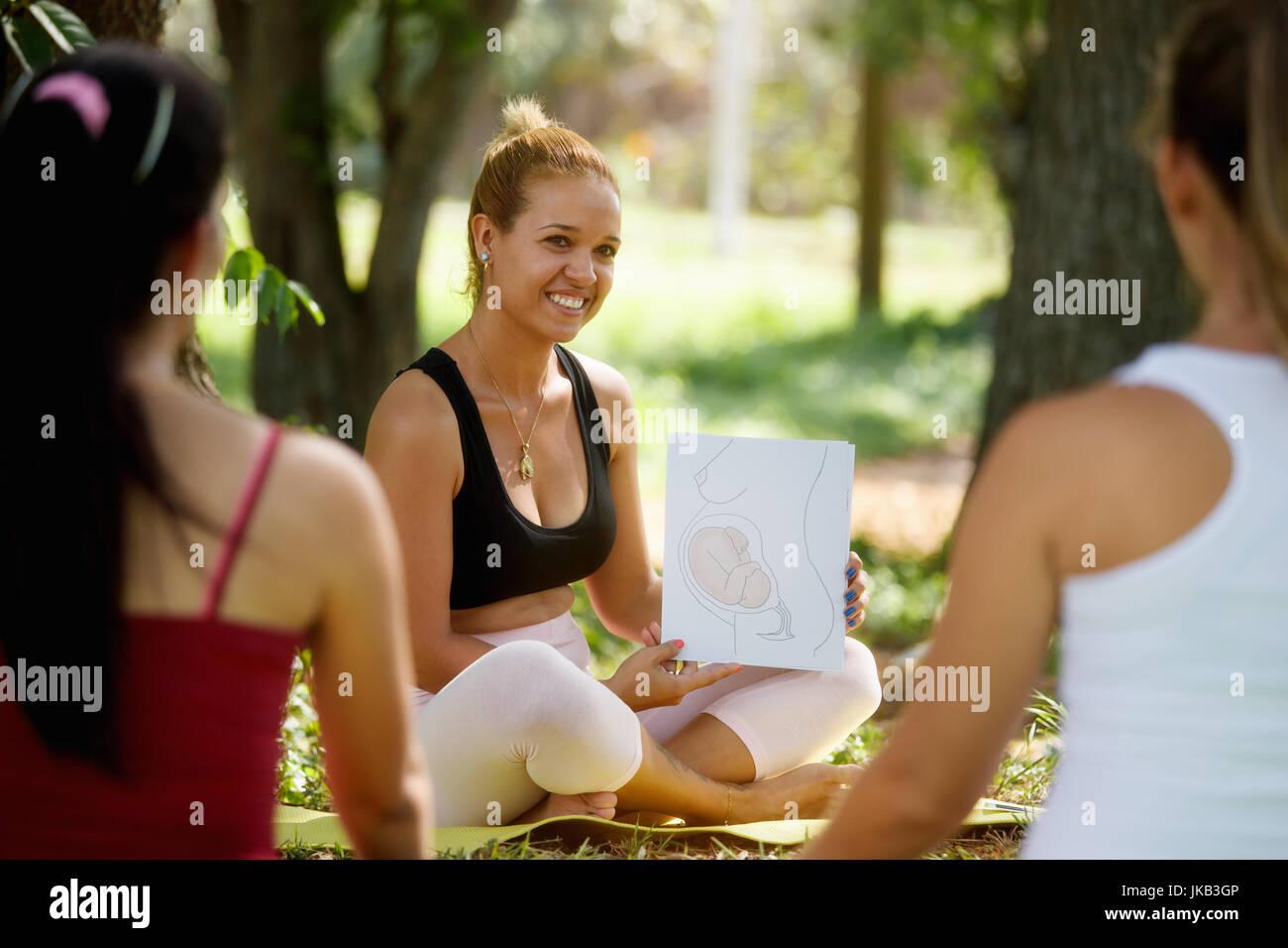 Schwangere Frauen, die pränatale Lektion im Park. Lehrer erklärt Wachstum des Babys im Bauch mit Bildern Stockbild