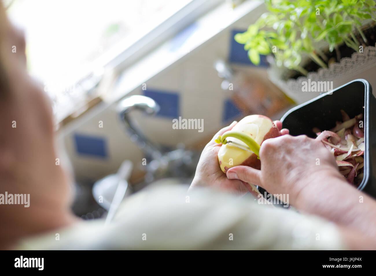 Ältere Frau rote Kartoffeln schälen Zubereitung von Speisen. Horizontale Ausrichtung mit selektiven Fokus Stockbild
