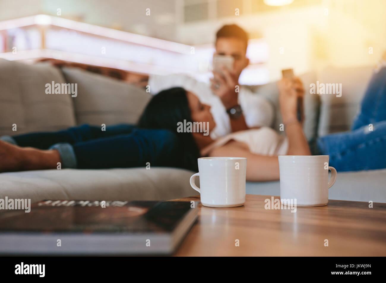 Zwei Kaffeetassen auf Tisch mit paar im Hintergrund auf Couch entspannen. Tassen Kaffee vorne mit Mann und Frau Stockbild