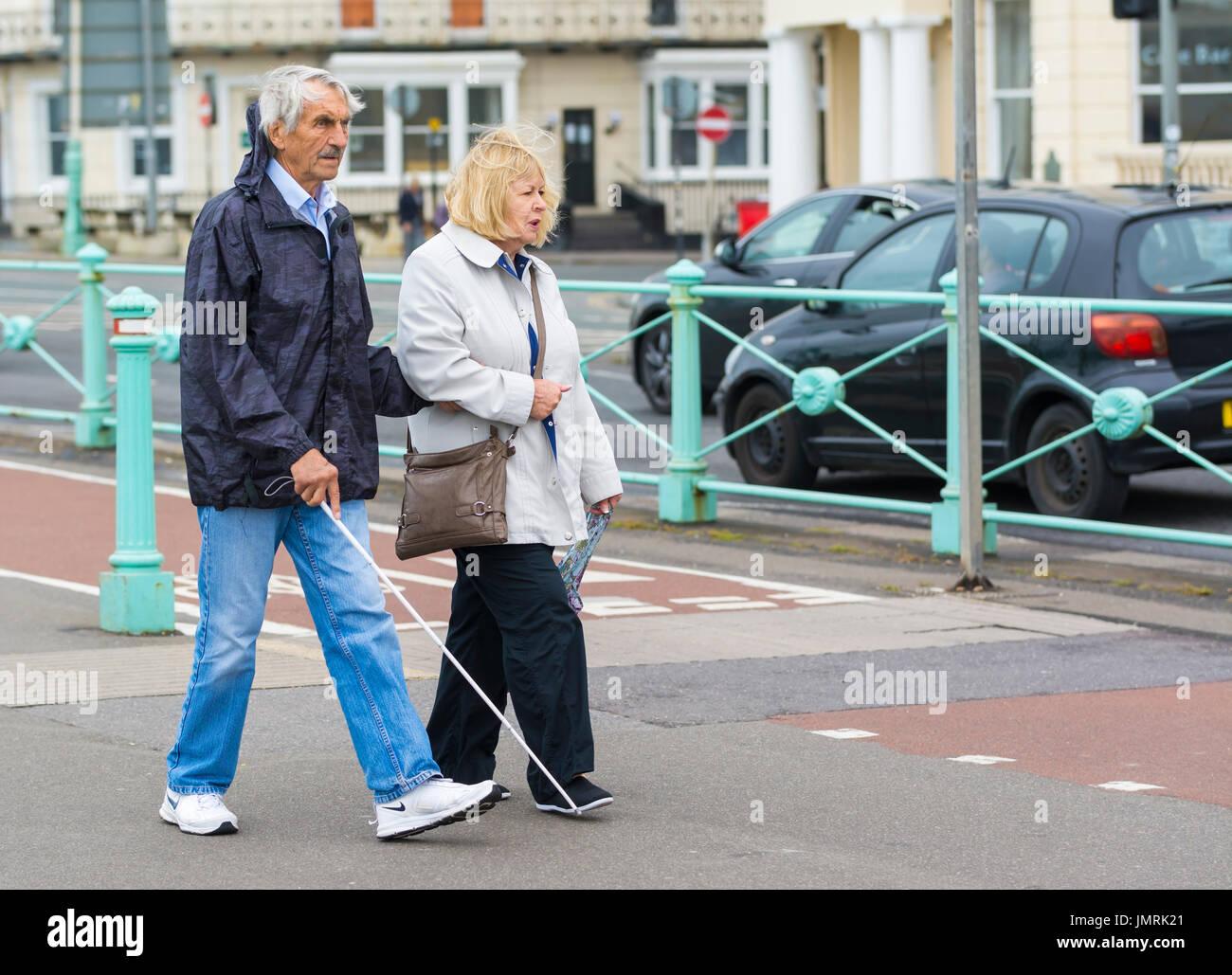 Ältere Menschen blinder Mann zu Fuß mit einem weißen Stock mit Hilfe von einer Dame. Stockbild