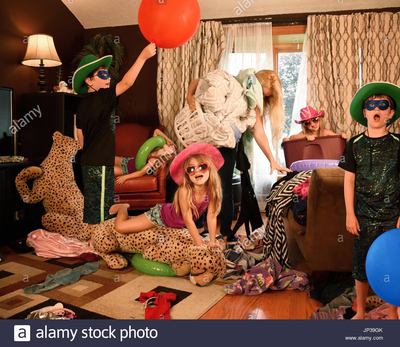Eine Hausfrau ist gestresst und müde Versuch, das Haus zu reinigen, während wilde Kinder ausgeführt Stockbild